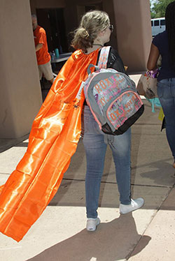 female student with orange cape carrying her new backpack