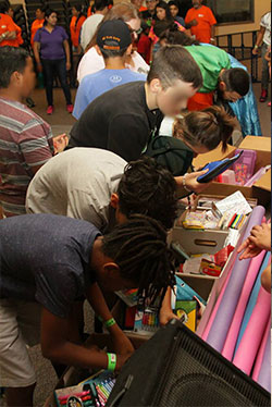 multiple kids looking through boxes filled with school supplies