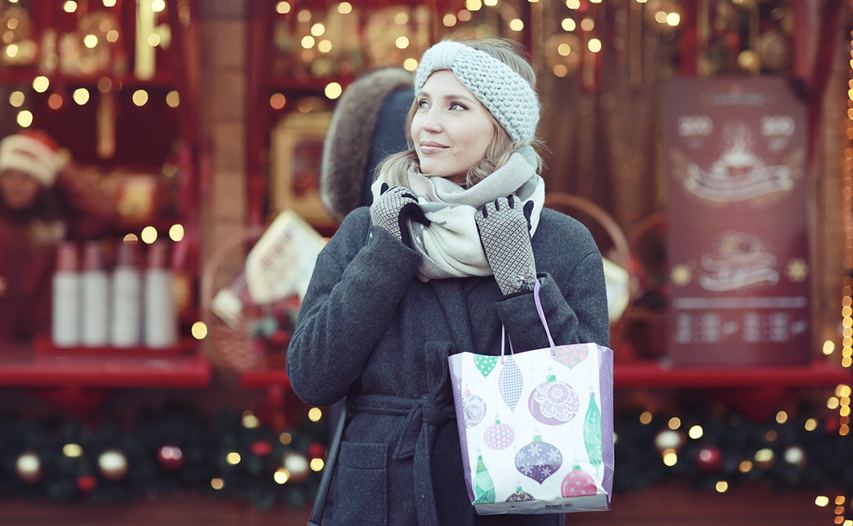 Female shopper adjusting scarf while carrying a Christmas shopping bag