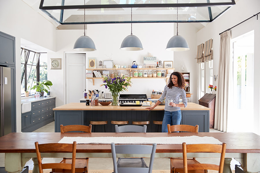 Smiling woman enjoying her open and inviting kitchen and dining area in her new home