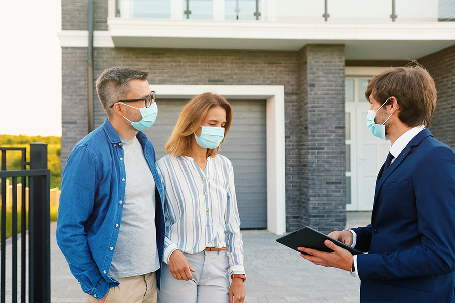 couple discussing mortgage options with realtor while wearing masks